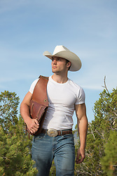 cowboy holding a saddle bag over his shoulder