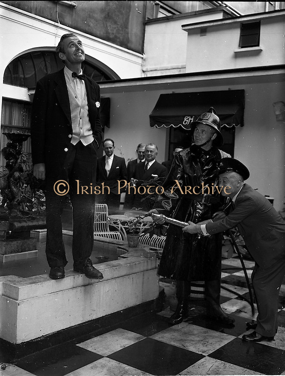 25/09/1958<br /> 09/25/1958<br /> 25 September 1958<br /> Dubtex - Prescott Reception. at the Gresham Hotel, Dublin. Image shows a demonstration of the water resistant or quick drying properties of trousers from Dubtex by having Jimmy O'Dea and a fireman spray it with a fireman's hose.<br /> Dubtex (Clothing) Ltd (Dublin Bespoke Clothing Ltd.) was based originally at 22 Wellington Quayo and had a factory called Dubtex House in Dolphins Barn, Dublin.