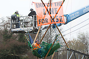 A bailiff uses a large cherry picker to approach Dan Hooper, widely known as Swampy during the 1990s, who is sitting on a bamboo tripod positioned in the river Colne on 8th December 2020 in Denham, United Kingdom. The climate and roads activist had occupied the tripod the previous day in order to delay the building of a bridge as part of works for the controversial HS2 high-speed rail link and a large security operation involving officers from at least three police forces, National Eviction Team enforcement agents and HS2 security guards was put in place to facilitate his removal.