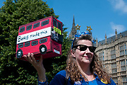A Remain protester holds a model bus, mocking Boris Johnson's claim that his hobby is making model buses outside Houses of Parliament, Westminster, London. June 26th.