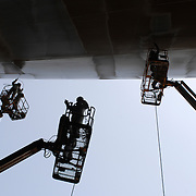 three workers lifted to the belly of a ship