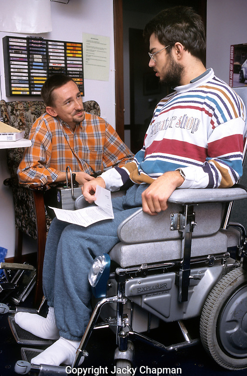 Helper in disabled center chatting with young man in wheelchair