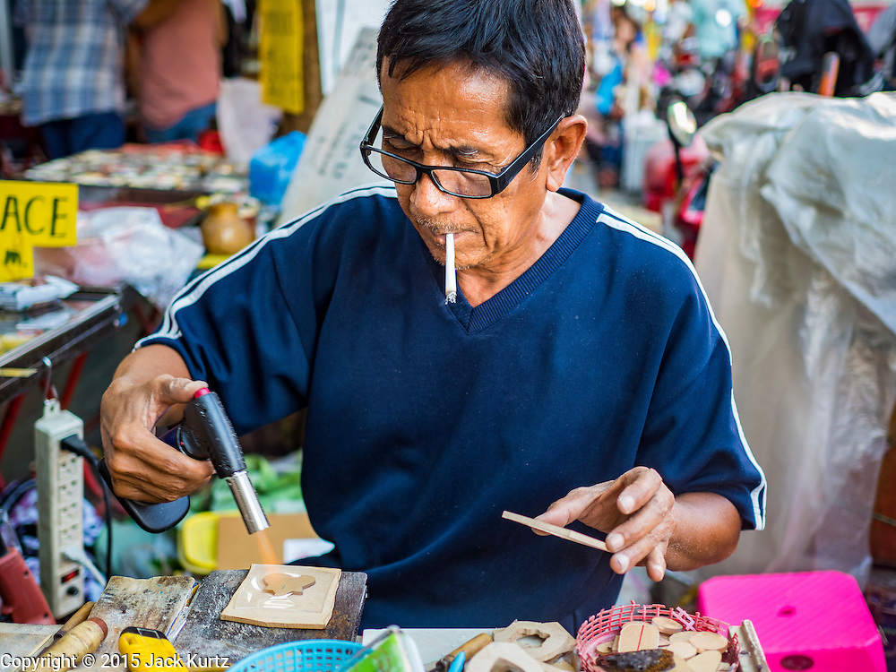 29 NOVEMBER 2015 - BANGKOK, THAILAND: A street vendor puts together cases for amulets in his market stall.  Hundreds of vendors used to sell amulets and Buddhist religious paraphernalia to people in the Amulet Market, a popular tourist attraction along Maharat Road north of the Grand Palace near Wat Maharat in Bangkok. Bangkok municipal officials announced that they are closing the market and forcing vendors to relocate to an area about one hour outside of Bangkok. The closing of the amulet market is the latest in a series of municipal efforts to close and evict street vendors and markets from areas that have potential for redevelopment. The street vendors were evicted from the area on Sunday, Nov. 29.      PHOTO BY JACK KURTZ