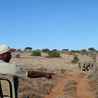 Africa, South Africa, Kwandwe. Spotter and Rhino at Kwandwe.
