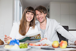 Portrait of couple having breakfast and reading newspaper together, smiling