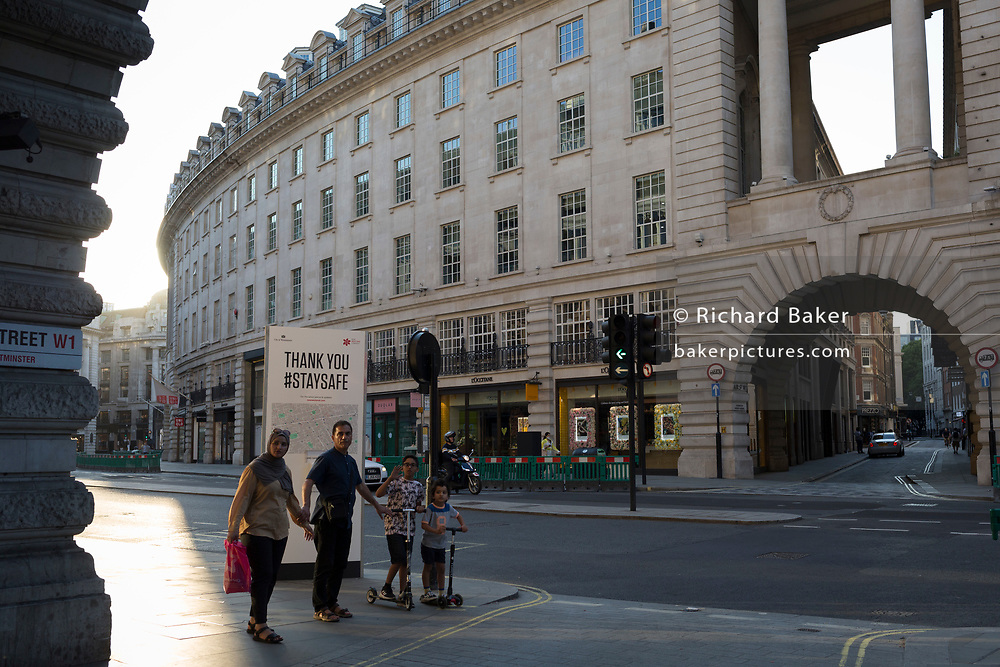 With a further 149 reported dying from Coronavirus in the last 24hrs, taking the UK death toll to 43,320, a family walks past social distance advice post with a hand sanitiser dispenser, on Regent Street during the Covid pandemic, on 25th June 2020, in London, England.