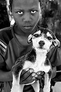 A boy is photographed with his puppy while he waits for it to receive treatment at a mobile clinic in Soul City, South Africa.  IFAW's CLAW program, provides veterinary services to cats and dogs in some of the poorest shantytowns outside of Johannesburg, South Africa.  2/23/12 Julia Cumes/IFAW