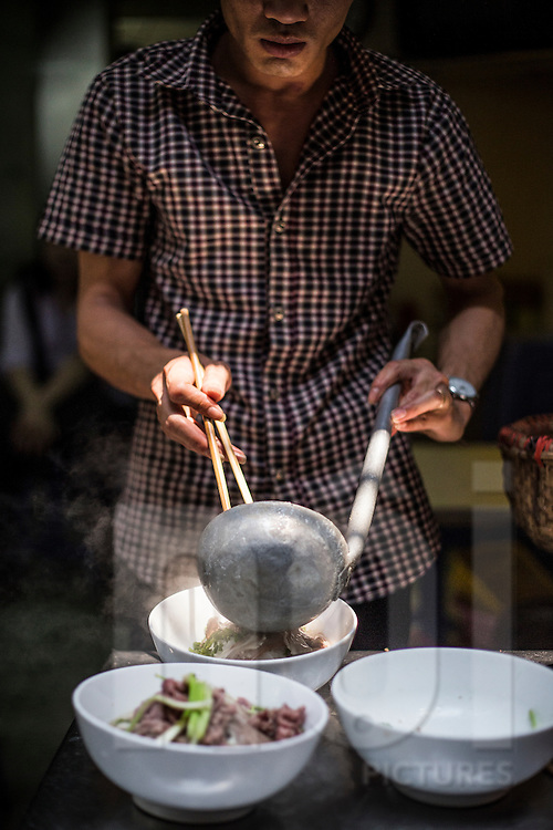 """A man pours broth in a bowl of traditional vietnamese dish """"beef noodle soup"""" (pho bo), Hanoi, Vietnam, Southeast Asia"""