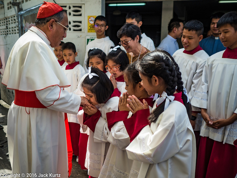 18 SEPTEMBER 2016 - BANGKOK, THAILAND:  Alter servers at Santa Cruz Church line up to kiss the ring of FRANCIS XAVIER KRIENGSAK, (left) the Archbishop of Bangkok, when he arrived to lead the church's 100th anniversary mass. Santa Cruz Church was establised in 1769 to serve Portuguese soldiers in the employ of King Taksin, who reestablished the Siamese (Thai) empire after the Burmese sacked the ancient Siamese capital of Ayutthaya. The church was one of the first Catholic churches in Bangkok and is one of the most historic Catholic churches in Thailand. The first sanctuary was a simple wood and thatch structure and burned down in the 1800s. The church is in its third sanctuary and was designed in a Renaissance / Neo-Classical style. It was consecrated in September, 1916. The church, located on the Chao Phraya River, serves as a landmark for central Bangkok.      PHOTO BY JACK KURTZ