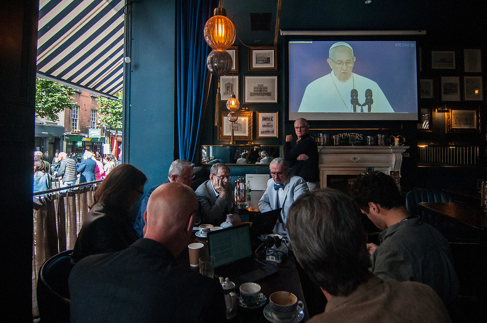 """Dublin, Ireland. 25th August, 2018. <br /> Bbc radio presenter Samuel Alwyline-Mosely looks at members of the worldwide association Ending Clergy Abuse preparing for the next interview, during Pope Francis speech during the first of the two-days of the visit of Pope Francis in Dublin, Ireland.<br /> Pope Francis has made a two-day visit to the Republic of Ireland by celebrating a Mass at Dublin's Phoenix Park. The Argentine Pope asked forgiveness for the """"abuses in Ireland, abuses of power, conscience and sexual abuses"""" perpetrated by Church leaders. It was the first papal visit to Ireland for 39 years. During his activities many activists, victims and survivors have made protests and a silent march Garden of Remembrance towards the last Magdalene Laundry to close in Ireland.<br />  © Simone Padovani"""
