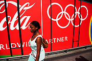 Area around Stratford in East London, home to the 2012 Olympic Games. People walking past the long stretch of Coca Cola sponsor advertising.
