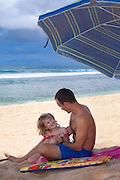 A little girl in her daddy's lap smiles happily at her father on the beach
