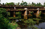 A man walks accross a bridge over the backwaters in Ayamenam in Kerala<br /> <br /> The Kerala backwaters are a chain of brackish lagoons and lakes lying parallel to the Arabian Sea coast (known as the Malabar Coast) of Kerala state in southern India. The network includes five large lakes linked by canals, both manmade and natural, fed by 38 rivers, and extending virtually half the length of Kerala state. The backwaters were formed by the action of waves and shore currents creating low barrier islands across the mouths of the many rivers flowing down from the Western Ghats range.<br /> The Kerala Backwaters are a network of interconnected canals, rivers, lakes and inlets, a labyrinthine system formed by more than 900 km of waterways, and sometimes compared to the American Bayou.[1] In the midst of this landscape there are a number of towns and cities, which serve as the starting and end points of backwater cruises