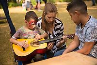 DEU, Deutschland, Germany, Berlin, 19.08.2015: Eine Freiwillige Helferin der Initiative Moabit Hilft bringt einem Flüchtlingskind das Gitarrespielen bei auf dem Gelände des Landesamts für Gesundheit und Soziales (LaGeSo), hier befindet sich die Zentrale Aufnahmeeinrichtung des Landes Berlin für Asylbewerber.