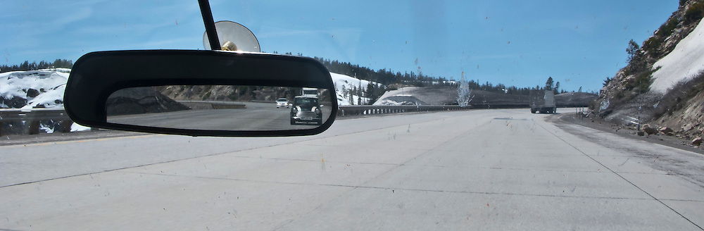 view out the windshield while climbing to Donner Pass in a classic Mini Cooper automobile with snow on the mountain slopes and another classic Mini Cooper in the rearview mirror   panorama