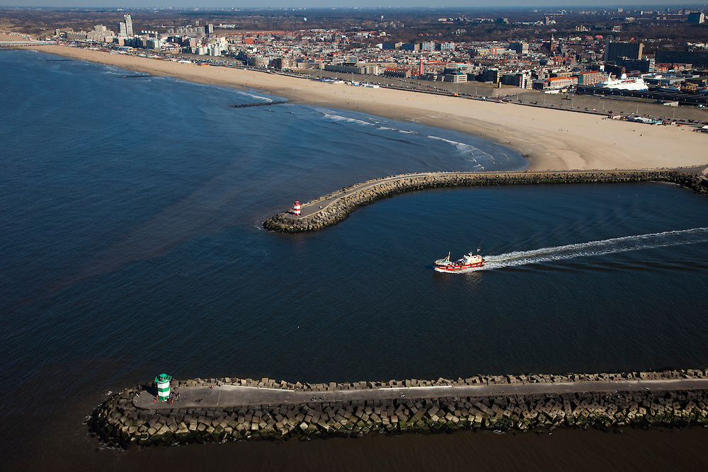 Nederland, Zuid-Holland, Scheveningen, 18-03-2009; Visserscheepje verlaat zeehaven en vaart tussen de havenhoofden naar open zee. Het voormalig vissersdorp, nu strand- en badplaats op het tweede plan, Den Haag centrum met skyline aan de horizon..Tiny fishing boat leaves port and sails between the piers to open sea. Former fishing village Scheveningen is now mainly a  seaside resort. In the background the skyline of The hague..Swart collectie, luchtfoto (toeslag); Swart Collection, aerial photo (additional fee required); .foto Siebe Swart / photo Siebe Swart
