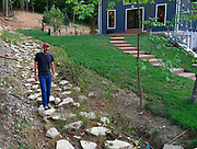 Steve Schatz walks along the original logging road that ran through the four acres he now owns. He added the boulders and made what looked like a creek into a natural drainage path for water runoff from the hilly land that surrounds his home. He and his wife Jennifer Schatz designed their rural Pacific home to resemble a Missouri dairy barn. <br /> Photo by Tim Vizer
