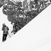 Forrest Jillson talks on his iPhone while Andrew Whiteford waits to drop into a backcountry line in the Tetons.