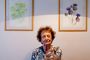 """Dita Kraus in front of her paintings in her flat in Prague Vinohrady. Born in Prague to a Jewish family in 1929, Dita Kraus has lived through the most turbulent decades of the twentieth and early twenty-first centuries. Here, Dita writes in her book """"A Delayed Life: The true story of the Librarian of Auschwitz"""" with startling clarity on the horrors and joys of a life delayed by the Holocaust. From her earliest memories and childhood friendships in Prague before the war, to the Nazi-occupation that saw her and her family sent to the Jewish ghetto at Terezín, to the unimaginable fear and bravery of her imprisonment in Auschwitz and Bergen-Belsen, and life after liberation."""