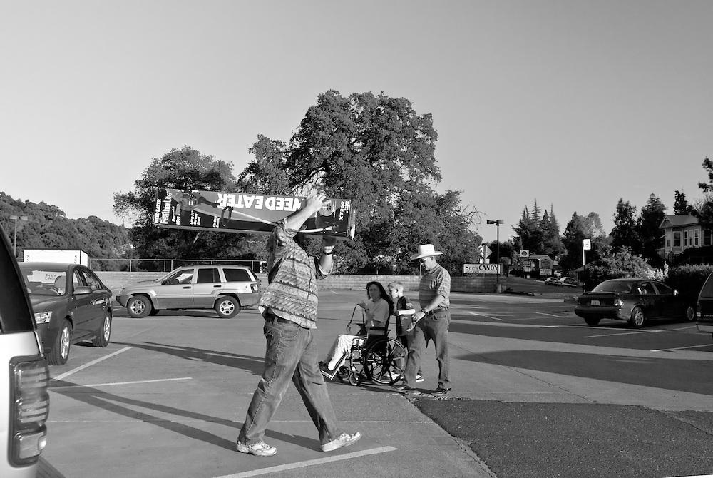 USA,Vereinigte Staaten von Amerika, Kalifornien, San Andreas, Ein Mann trägt einen Karton mit einem so genannten weed eater, einem Unkrautvernichter über den Parkplatz eines Supermakts |  USA ,United States,United States of America,California, San Andreas, In front of a supermarket a man is carrying a box with a so called weed eater    |