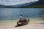 A baby is passed into a rowing boat at a shore of Lake Bohinj near Ucanc, on 19th June, in Lake Bohinj, Sovenia