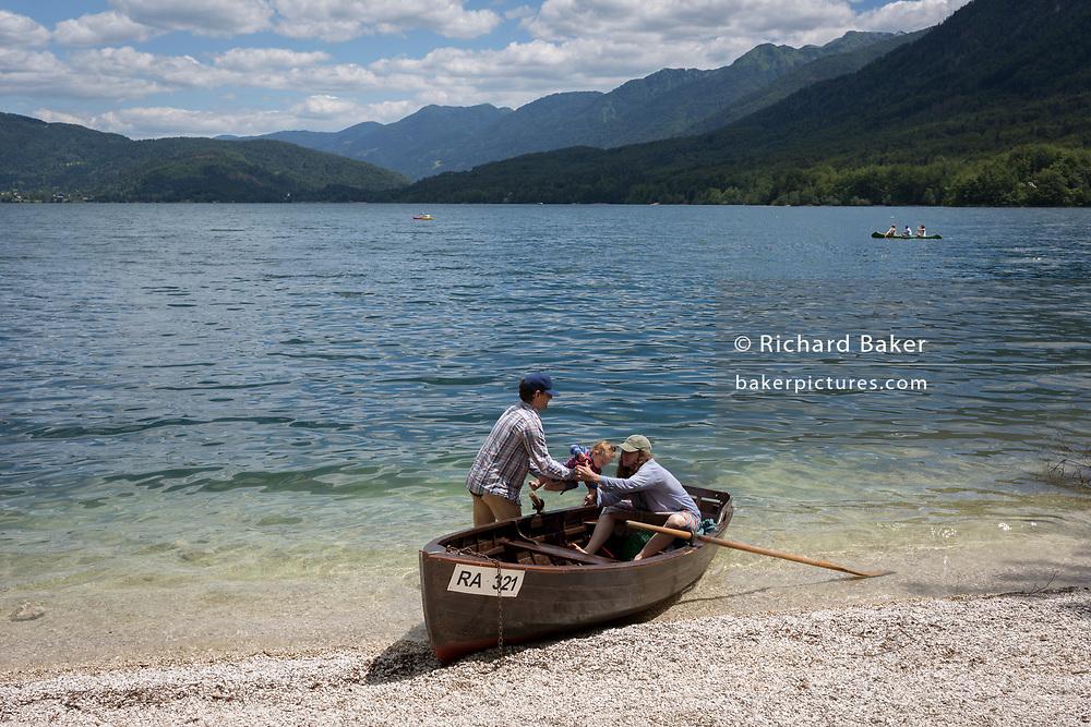 A baby is passed into a rowing boat at a shore of Lake Bohinj near Ucanc, on 19th June, in Lake Bohinj, Sovenia