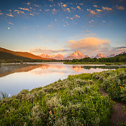 The sun rises through the clouds at Oxbow Bend in Grand Teton National Park, Wyoming.