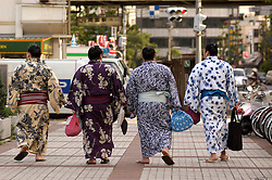 Four sumo wrestlers in kimono walking in Tokyo after competition