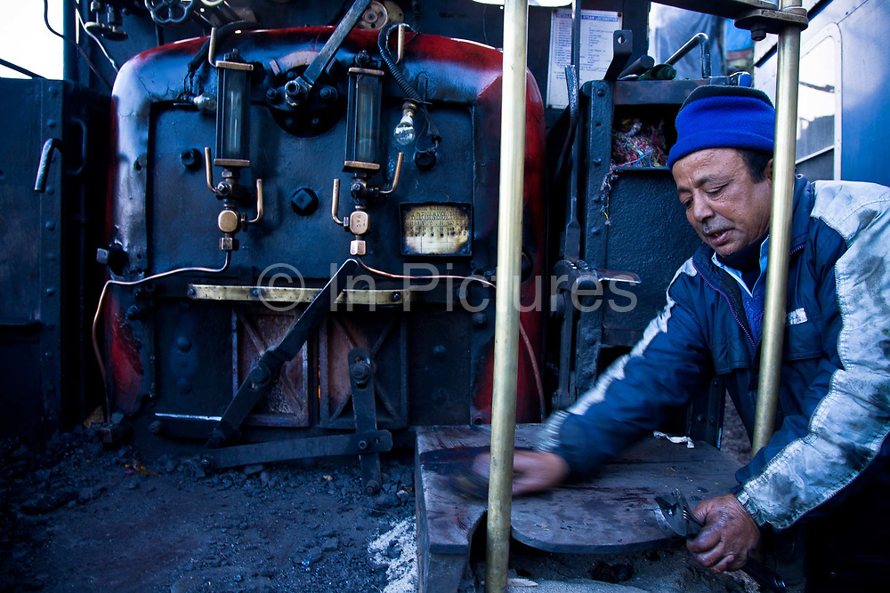 """Train driver Birkh Dattani drives the narrow gauge steam train between Darjeeling and Kurseong, the shorter of the two  journeys he has been traveling for the past  40 years. The Darjeeling Himalayan Railway, nicknamed the """"Toy Train"""", is a narrow-gauge railway from Siliguri to Darjeeling in West Bengal, run by the Indian Railways. It was built between 1879 and 1881 and is about 86 km long. The elevation level is from about 100 m at Siliguri to about 2200 m at Darjeeling. It is still powered by a steam engine and travels daily between the two towns, as well as a shorter route to Kurseong.  It is now classed as a World Heritage Site by UNESCO. India."""