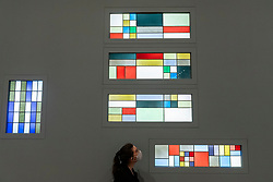 © Licensed to London News Pictures. 13/07/2021. LONDON, UK. A staff member views a collection of stained glass compositions (1927 & 1928).  Preview of the first UK retrospective exhibition at Tate Modern of works by Sophie Taeuber-Arp (1889-1943), one of the foremost abstract artists and designers of the 1920s and 30s. Works from Taeuber-Arp's accomplished career as a painter, architect, teacher, writer, and designer of textiles, marionettes and interiors is on 15 July – 17 October 2021.  Photo credit: Stephen Chung/LNP