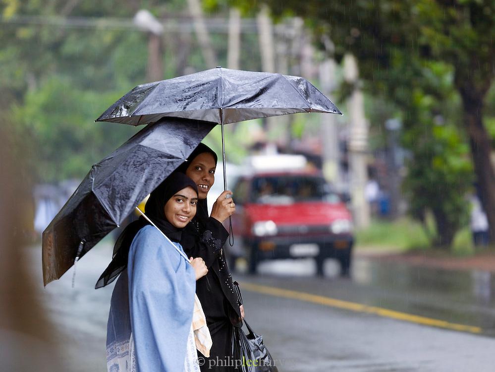 Women shelter under umbrellas during the monsoon rain, Cochin, Kerala, India