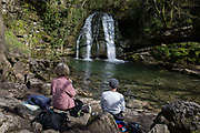 A picnic couple of walkers sit on rocks, admiring the Yorkshire Dales waterfall called Janets Foss on 12th April 2017, in Malham, Yorkshire, England. Janets Foss is a small waterfall in the vicinity of the village of Malham, North Yorkshire, England. It carries Gordale Beck over a limestone outcrop topped by tufa into a deep pool below. The pool was traditionally used for sheep dipping, an event which took on a carnival air and drew the village inhabitants for the social occasion. The name Janet sometimes Jennet is believed to refer to a fairy queen held to inhabit a cave at the rear of the fall. A foss is an old Norse word meaning waterfall.