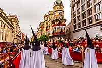 Hooded Penitents (Nazarenos) in the procession of the Brotherhood (Hermandad) La Sed, on Avenue de la Constitucion (with the rounded Adriatic Building (Edificio de la Adriatica) behind,  Holy Week (Semana Santa), Seville, Andalusia, Spain.