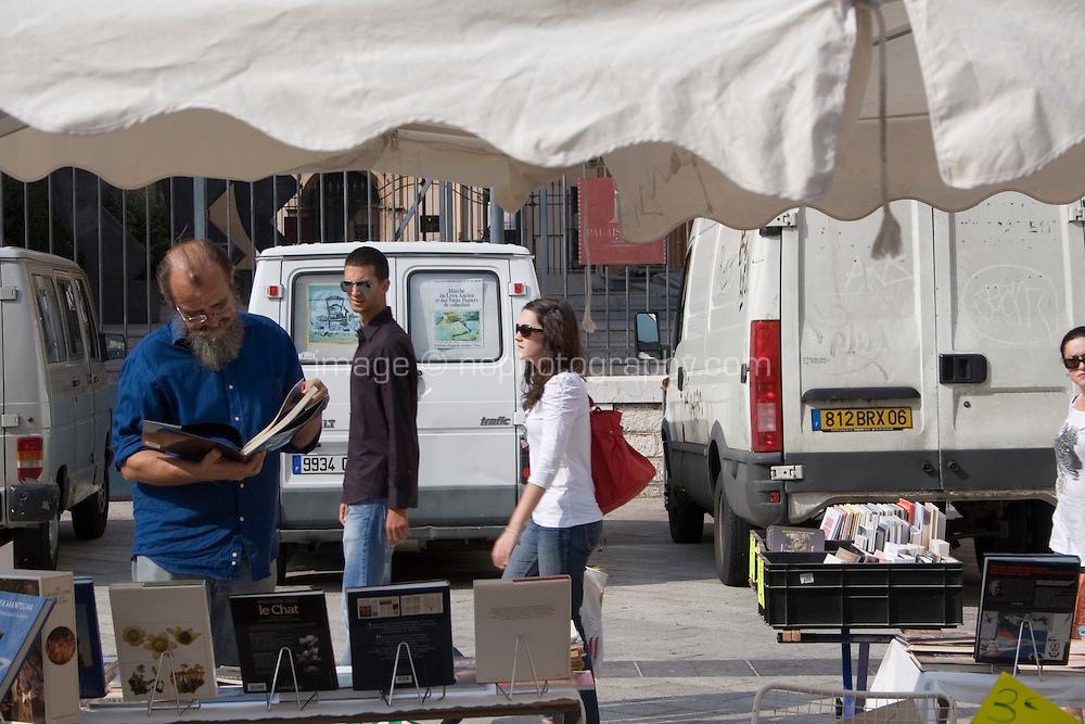 Man browsing a book stand in Place du Palais in the old town in Nice the South of France