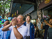 "16 JANUARY 2013 - BANGKOK, THAILAND:   SUKHUMBHAND PARIBATRA, candidate for Governor of Bangkok, ""wais"" (the ""wai"" is a traditional Thai greeting) voters as he during a campaign function on Silom Road in Bangkok. The Oxford educated Sukhumbhand is a member of the Thai royal family (he is a great grandson of the late Thai King Chulalongkorn). He is a member of the Thai Democrat party and was first elected Governor of Bangkok in 2009. He is running for reelection this year. Sukhumbhand faces six challengers in the March 3 election. His toughest opponent is expected to be Police General Pongsapat Pongcharoen, who is running under the banner of the Pheu Thai Party, which controls the Prime Minister's office and Parliament.   PHOTO BY JACK KURTZ"