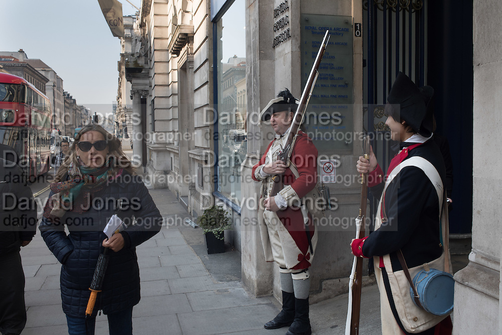 L On left: Member of the Red Coats and Revolutionary Society with a real gun, on right a Sales assistant from the Mint London office with a replica gun, aunch of the WORLD'S MOST EXPENSIVE COIN ARRIVing  IN LONDON - FLOWING HAIR SILVER DOLLAR, Amon Carter' Flowing Hair Silver Dollar, the first dollar to be minted in the U.S., ,Royal Opera Arcade,  Pall Mall, 17 March 2016
