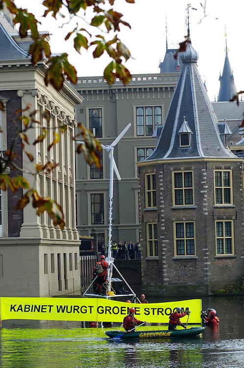 Nederland, Den Haag, 12 okt 2005..Aktievoerders van Greenpeace hebben een windmolen geplaatst in de hofvijver, vlak voor het torentje van Balkenende..Op een spandoek staat.Foto (c) Michiel Wijnbergh