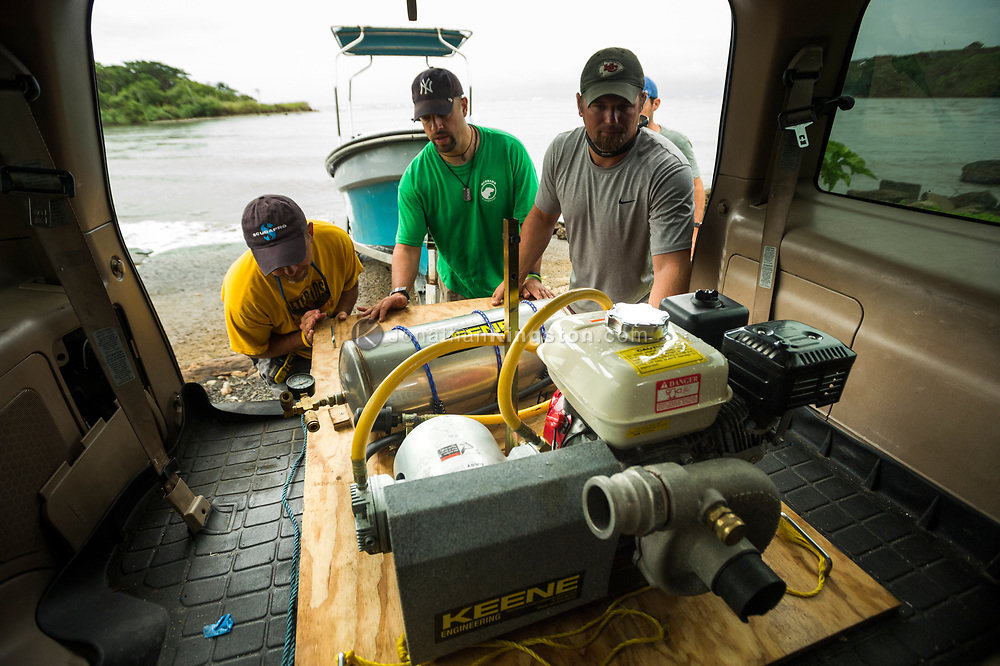Men unloading a diving air compressor and dredge unit in Panama. (Model Released)