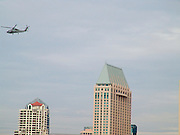 A helicopter flying low over high rise.