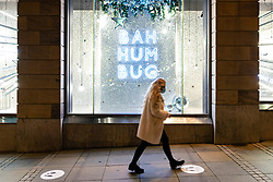 Edinburgh, Scotland, UK. 14 December 2020. City of Edinburgh controversially remains in Level 3 of lockdown meaning bars and restaurants must close at 6pm and not sell alcohol. Most bars have chosen to remain closed, Tuesday will see Scottish Government announce if the city will relax lockdown to level 2 or remain at level 3. Pic; Shop window display at Harvey Nichols with Bah Hum Bug message in lights.  Iain Masterton/Alamy Live News