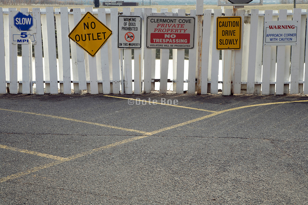 many traffic and warning signs on a wooden fence