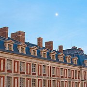 Moon over front wing of Palace of Versailles, France