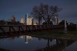 Houston Skyline at night reflected in water at Buffalo Bayou Park.