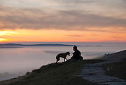 A walker and his dog pause for a break on Mam Tor, Peak District