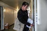 Singaporean volunteer Nicolas Oh posts leaflets for a local community support group called Mutual Aid through letter boxes on a housing estate near the Caledonian Road in North London on 17th March 2020. Mutual Aid and other community support groups have grown significantly in the last few days as people volunteer to help their neighbours who are vulnerable or self isolating with things like shopping, getting prescriptions, and providing meals.  via Getty Images.