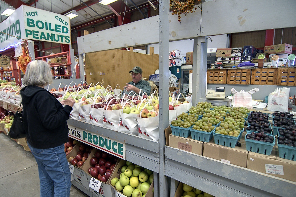 A woman shops for fresh fruit at Jarvis Produce at the Western North Carolina Farmer's Market in Asheville, NC on Sunday, November 3, 2013. Copyright 2013 Jason Barnette<br /> <br /> The WNC Farmer's Market is open daily year-round, providing a place for local farmers and artisans to sell their goods throughout the year. The market was opened in 1977 and consists of 38,000 square feet of retail space, five open-air truck sheds with 194 spaces, a small dealers building, and two wholesale buildings.