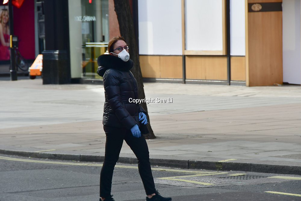 A Asian woman wearing a mask at street during Coronavirus - Pandemic hit Oxford Street many shops closure a few open but empty on 21 March 2020, UK.