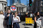 A young man and woman hold their coffees both with erect index fingers on their coffee cups, outside one entrance of Bank Underground Station in the City of London, the capital's ancient, financial district, on 14th May, in London, England.