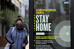 © Licensed to London News Pictures. 30/12/2020. London, UK. A woman wearing a face covering walsk past the government's 'Coronavirus Tier 4 - Stay Home' publicity poster in north London, as the Medicines and Healthcare Products Regulatory Agency (MHRA) approves the Oxford/AstraZeneca vaccine (codenamed AZD1222 or ChAdOx1) for use in the UK. Health Secretary Matt Hancock has said that the vaccine will be rolled out from 4 January 2021. A number of cities will be put into tougher Tier 4 COVID-19 restrictions after the mutated SARS-Cov-2 virus continues to spread around the country and coronavirus infection rates rise. Photo credit: Dinendra Haria/LNP