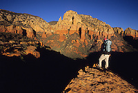 A backpacker admires the view while hiking in the Coconino National Forest near Sedona, Arizona.